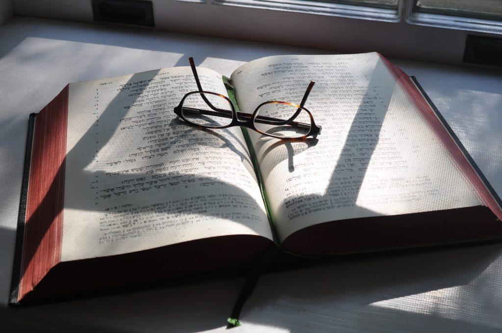 aufgeschlagene hebräische Bibel mit Brille